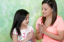 Mother and daughter in prayer.