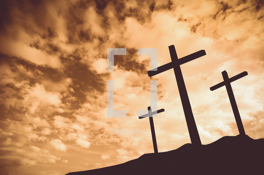 silhouettes of three crosses on a hill