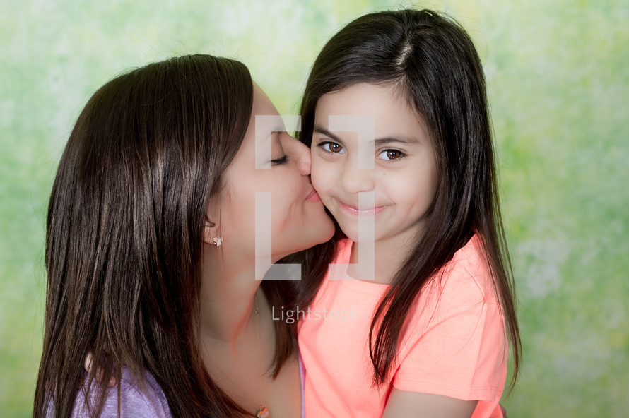 mother kissing her daughter on the cheek