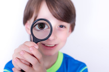 Boy with a magnifying glass to his eye.
