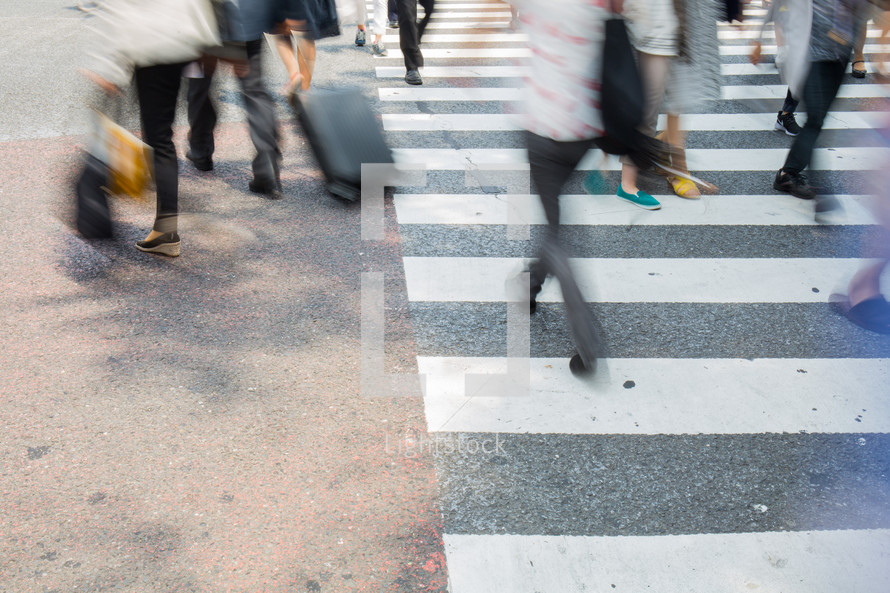 blur of people crossing a crosswalk