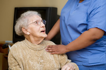 Hands of a caregiver touching the shoulder of an elderly woman in a wheelchair.