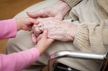 Child's hands holding the hands of a grandmother in a wheelchair.