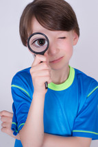 Boy looking through a magnifying glass.