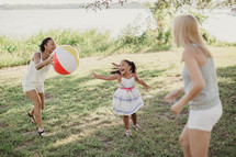 Two women and a little girl playing outdoors with a beach ball.
