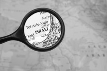 Magnifying glass on a map of the Middle East.