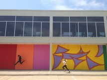 man and woman running and jumping in front of abstract painted walls