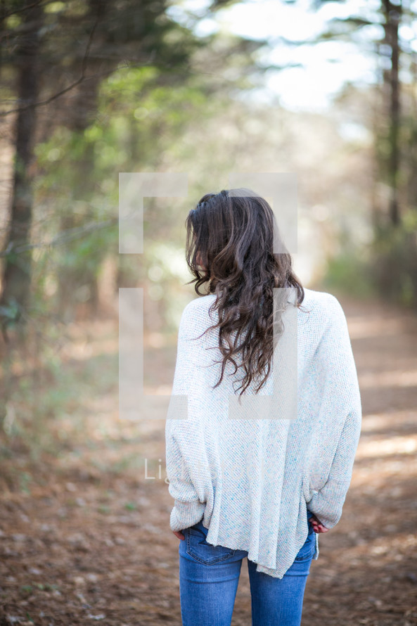 woman in a sweater walking on a path in a forest