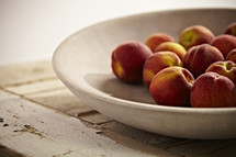 Peaches in a bowl sitting on a wooden table