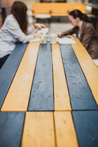 women discussing the Bible while sitting at a picnic table outdoors