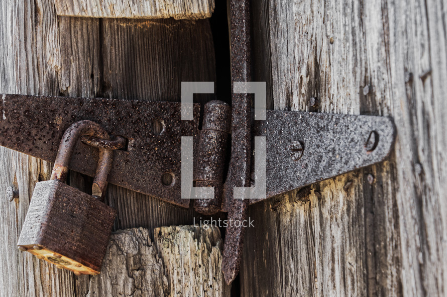 An old padlock on a rusted latch attached to an old door textured with age. Possible themes: old vs. new, freedom.