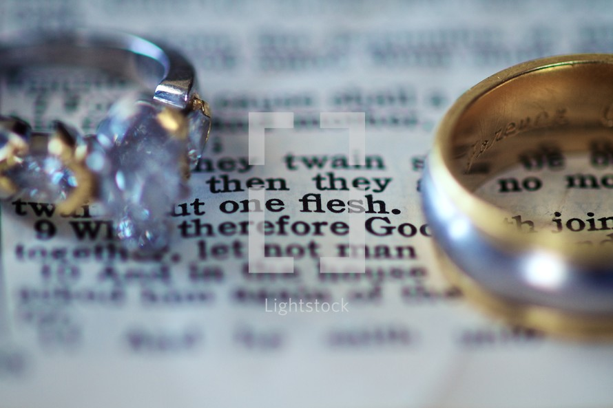 Wedding rings lying on a page of the bible - Mark 10:8
