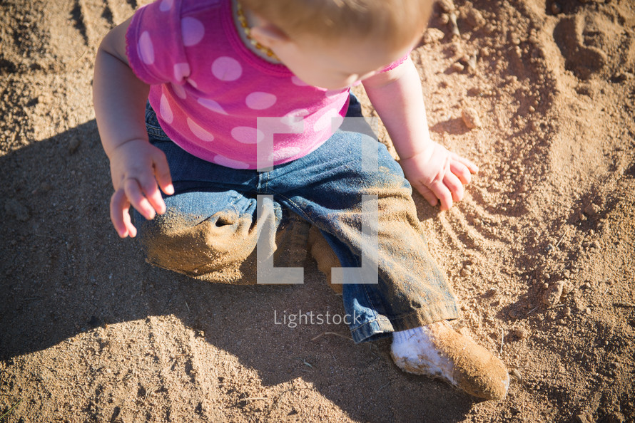 A baby sitting and playing in sand.