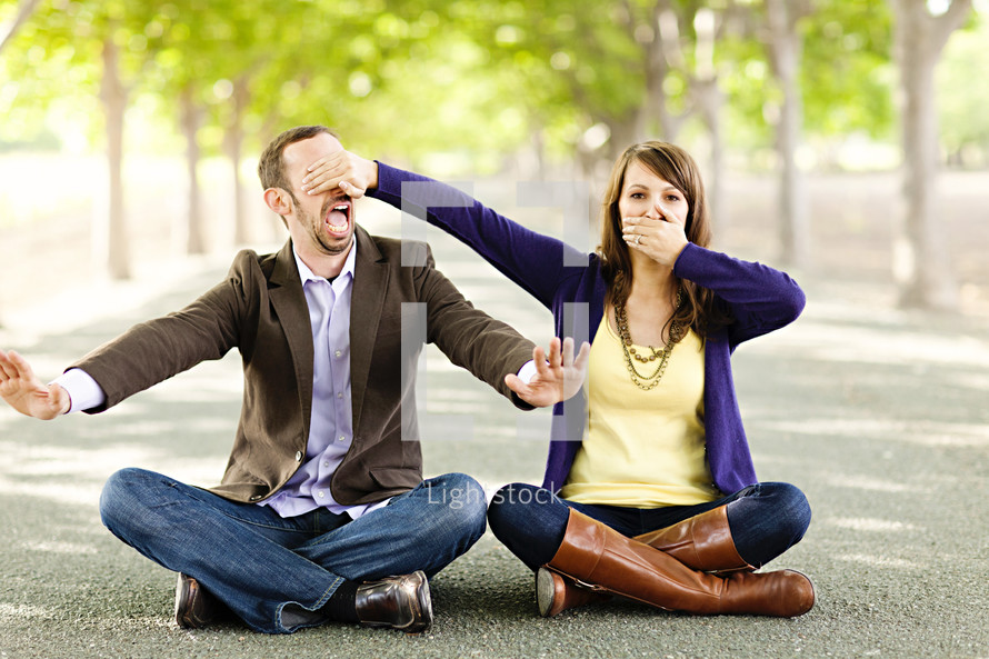 ear no evil speak no evil young engaged couple sitting indian style on ground
