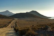 girls walking on a dirt road through the desert