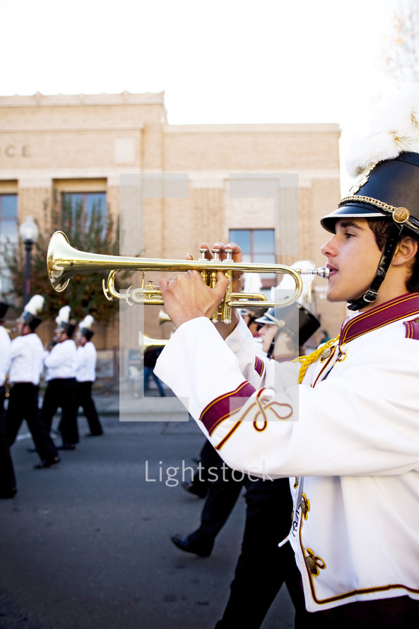 Boy playing trumpet with school band marching on street competition  brass