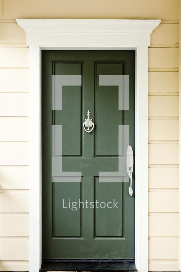 A green door with a door knocker.