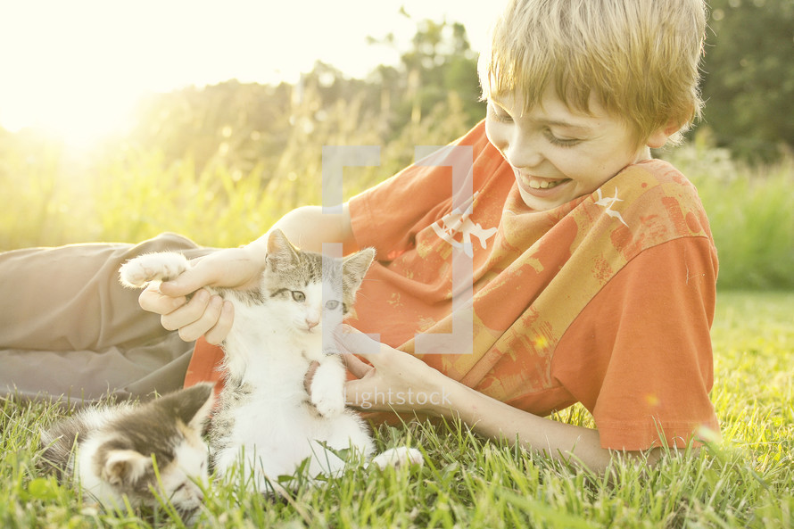 A boy playing with kittens.