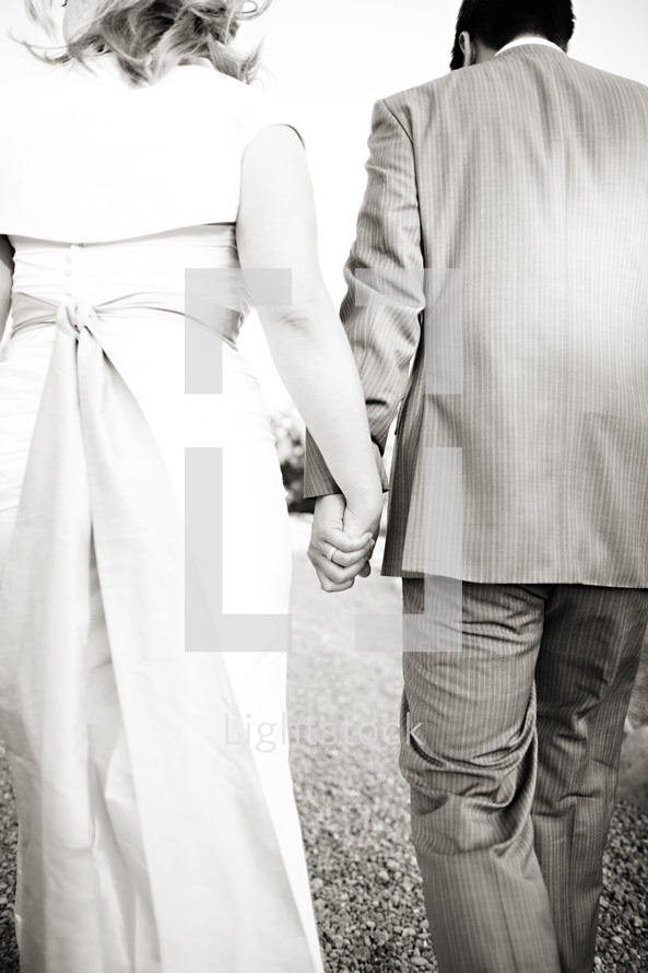couple walking holding hands bride and groom wedding
