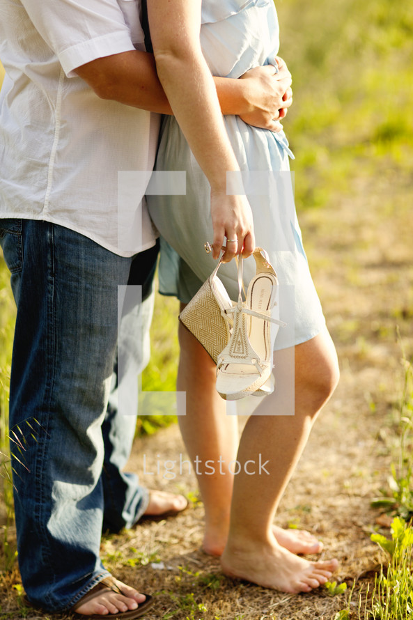 Happy couple man & woman in sandles bare feel holding shoes in hand