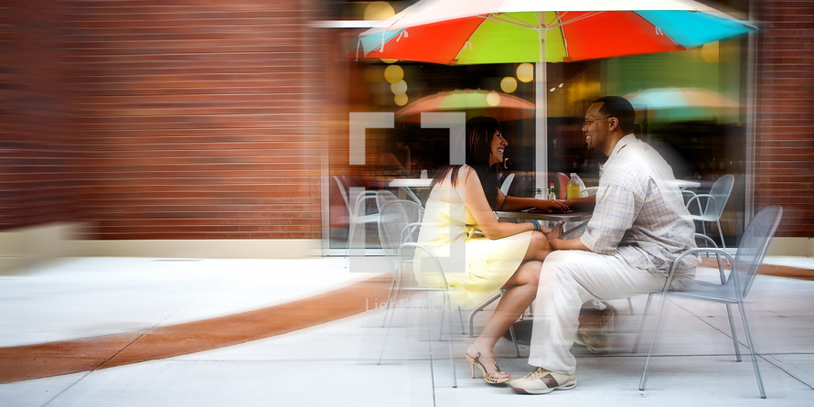 Couple eating lunch under table umbrella