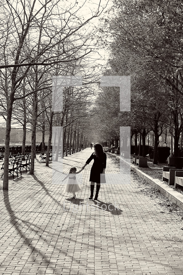 mother walking with her daughter  in a park