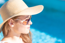 a woman in a sunhat sitting by a pool