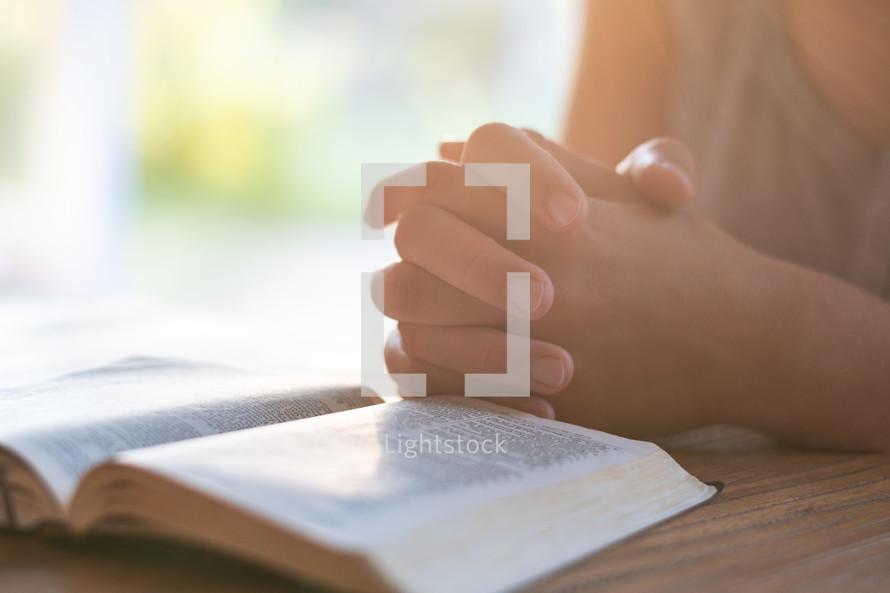 praying hands beside of a Bible