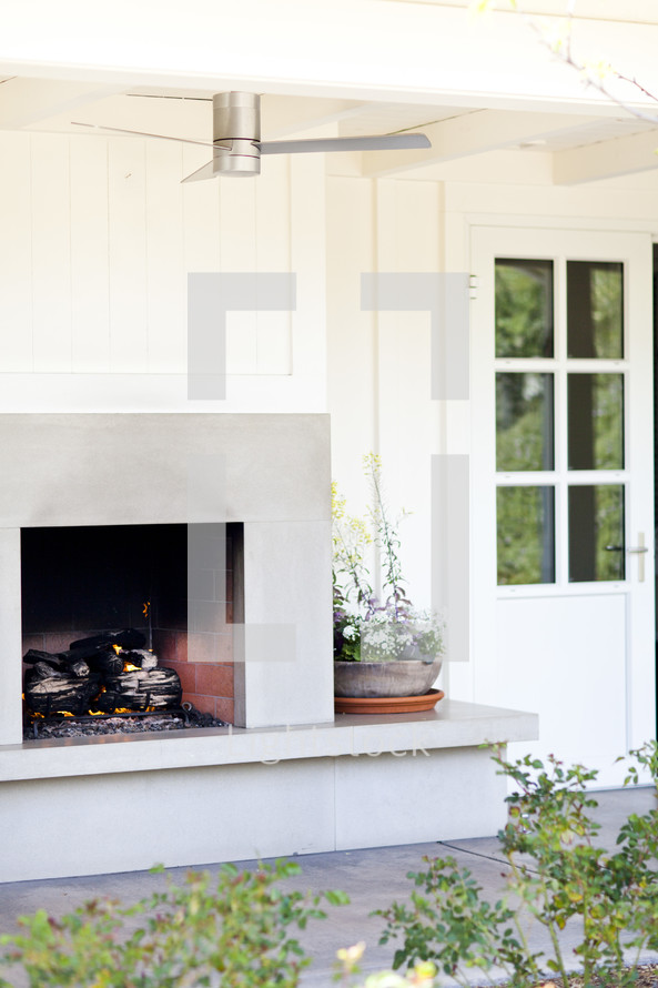fire burning in an outdoor fireplace  patio, resort ceiling fan