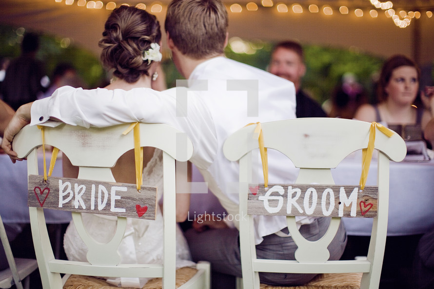 bride and groom sitting at reception - embracing