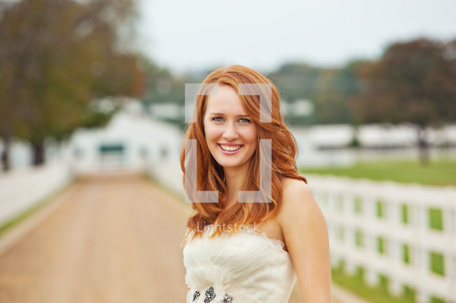 girl standing in a country lane - picket fence