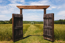 Open wooden gate doors leading to a pasture.
