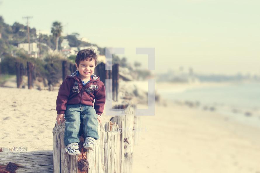 Child sitting on old wood pillars on a beach.