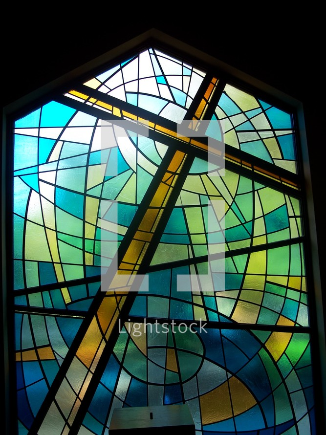 The power of the cross - Stained glass window art of the cross of Christ in shades of blue, green, gold and yellow showing the redeeming power of the Cross where Jesus was crucified and slain for the sins of mankind.