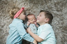 big brother and big sister with their newborn baby brother