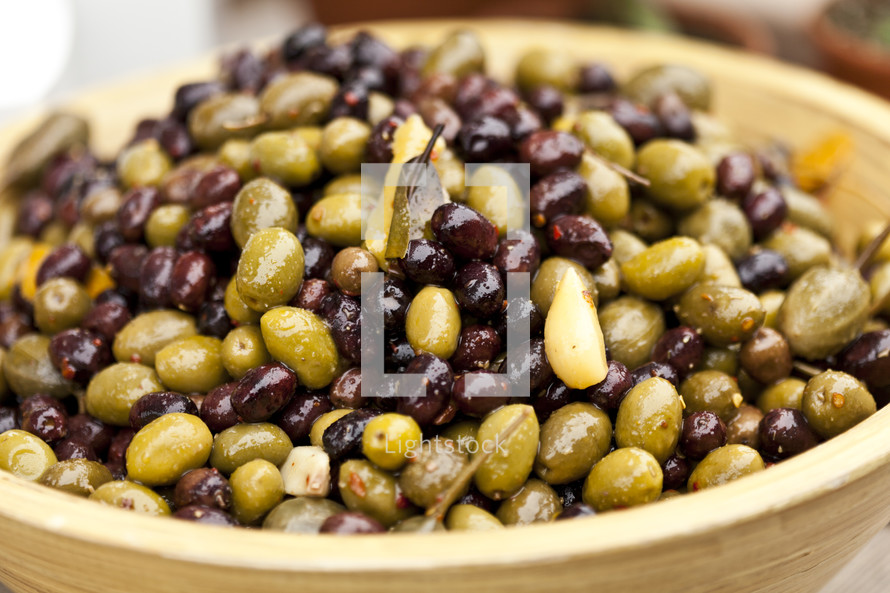 Bowl of black and green olives with garlic cloves and bay leaves.