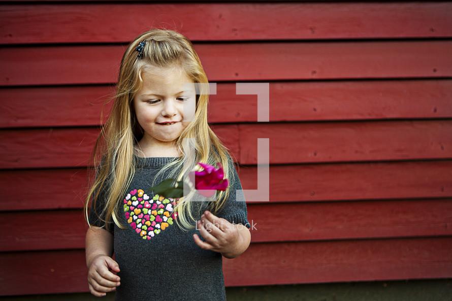 girl holding flower standing against wood plank wall