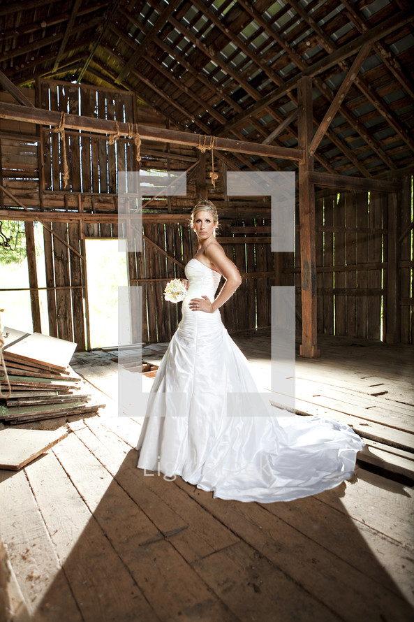 bride standing in an old barn