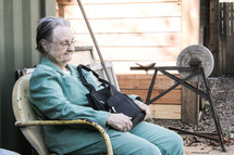 An elderly woman sitting in a chair holding her purse