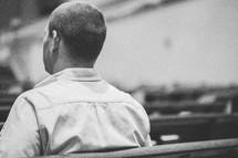 Man sitting in a church pew.