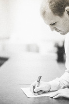 Man with pen in hand writing on a piece of paper.
