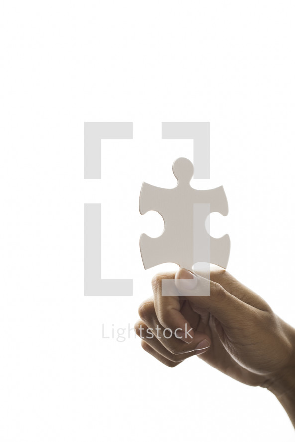 a hand holding up a puzzle piece