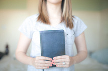Woman holding a clsoed Bible.
