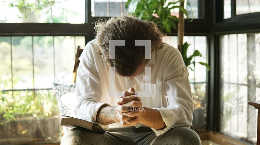 a man bowing his head in sincere prayer