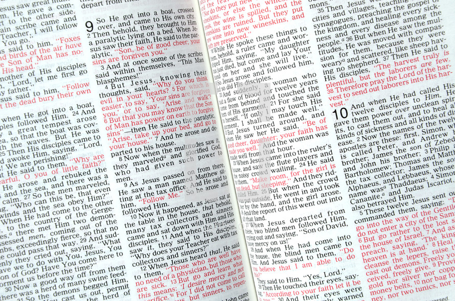 red text scripture on the pages of a Bible