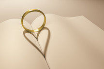 wedding band forming a heart shadow between the pages of a book