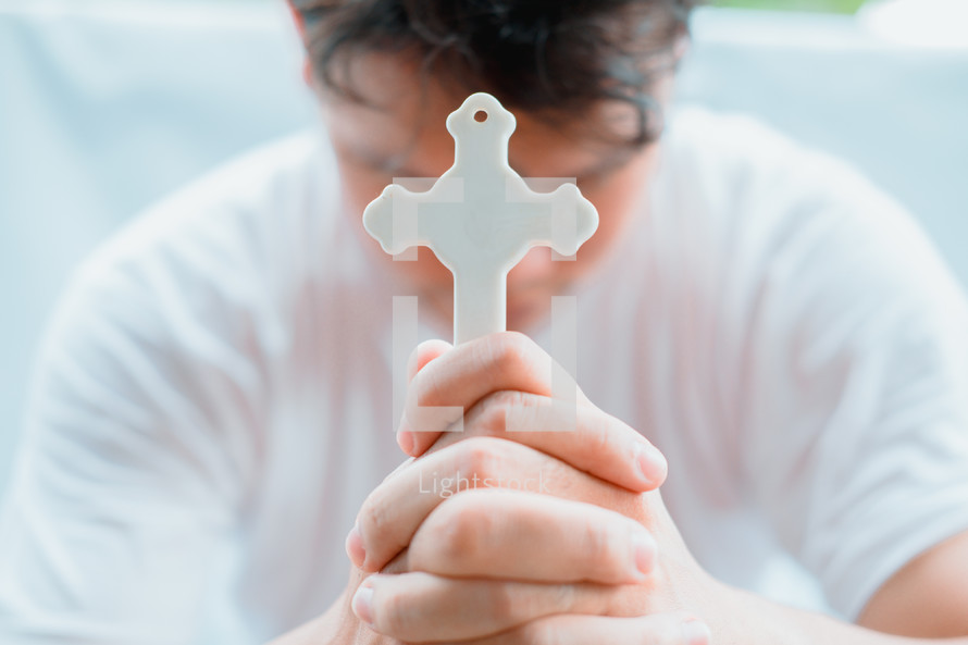 a man holding a cross praying with head bowed