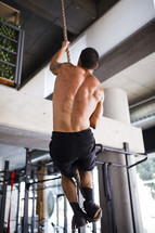 a man climbing a robe in a gym