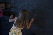 a toddler girl drawing a heart on a chalkboard