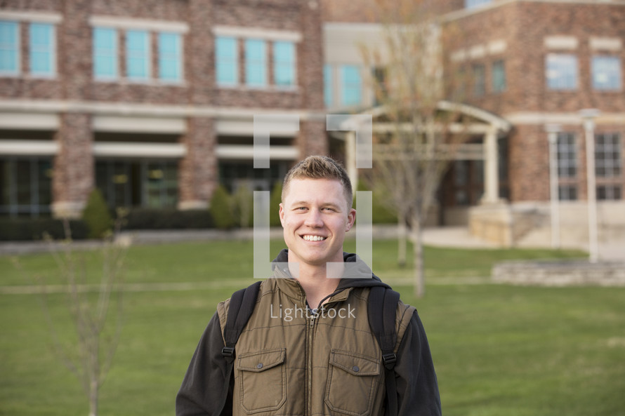 young man with a book bag on campus